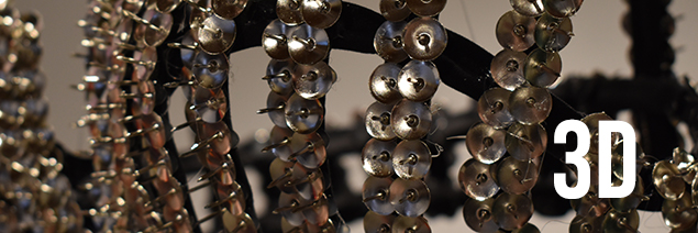 close up shot of a bra made out of tacks, with 3d written over it